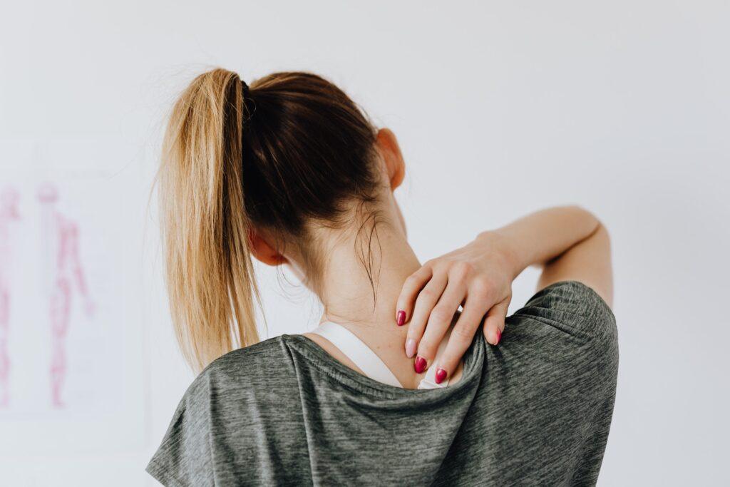 En tjej masserar sin värkande nacke