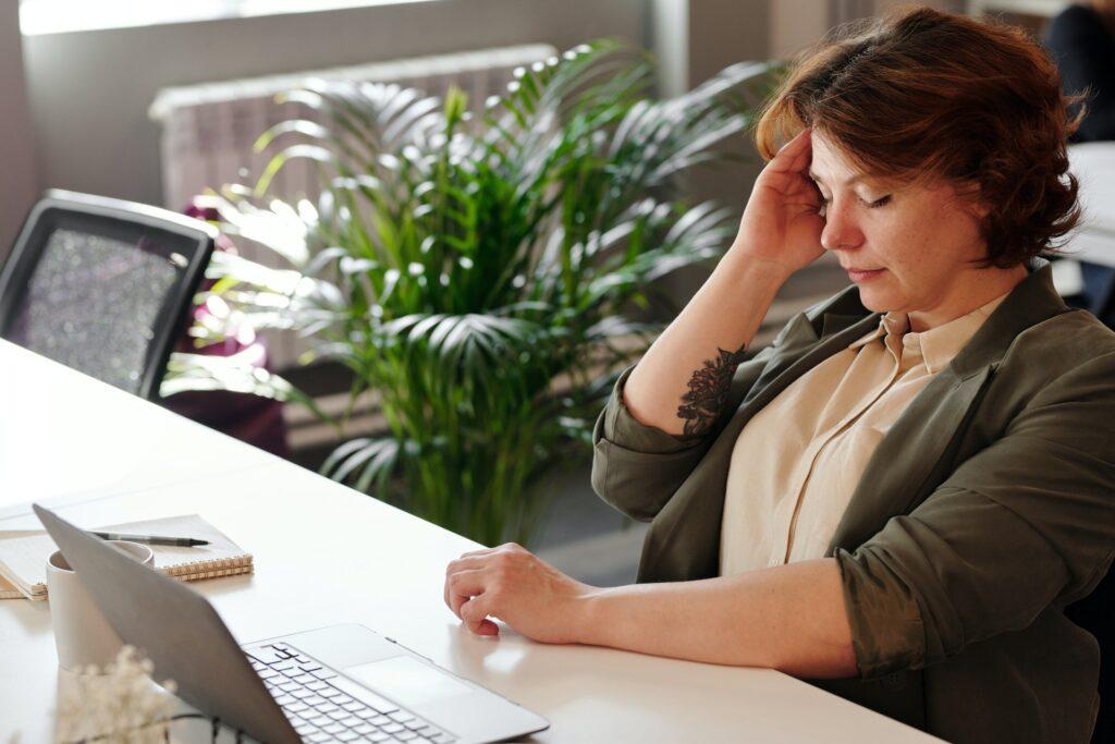 En kvinna sitter och jobbar men håller sig för tinningen och ser ut att ha ont
